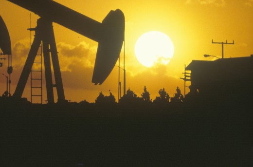 Oil drilling well silhouetted at sunset : Stock Photo