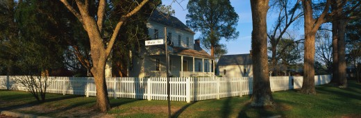 This is a photo of a typical suburban house on Main Street, USA. There is a white picket fence on a shaded, tree lined street with a green lawn. At the corner is a street sign that says, Main Street & Front Street. This is the Bonner House which was built in 1820. The town of Bath was founded in 1690. : Stock Photo
