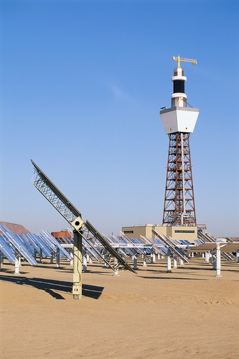 Stock Photo: 1599R-16197 Solar panels at solar energy plant with pylon and building in background