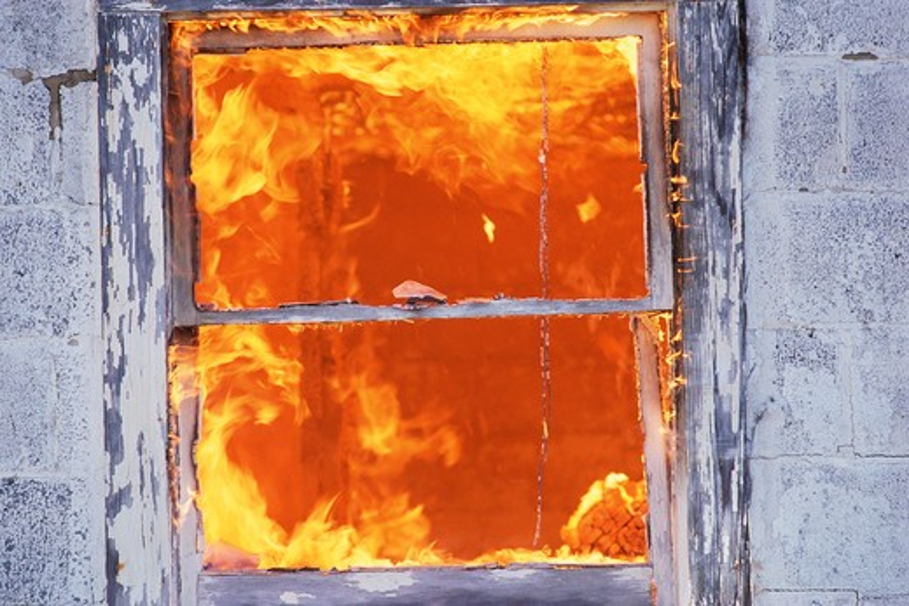 Fire seen through building window : Stock Photo