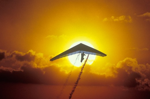 Solar Sailing Hang Gliding in sunset silhouette : Stock Photo