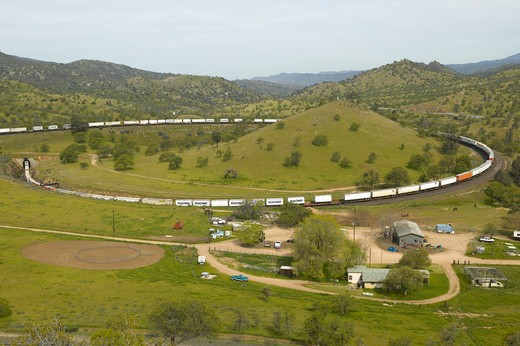 The Tehachapi Train Loop near Tehachapi California is the historic location of the Southern Pacific Railroad where freight trains gain 77 feet in elevation and show freight cars traveling in giant loop : Stock Photo