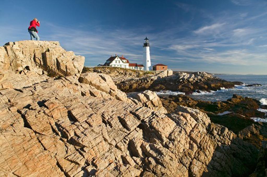 Stock Photo: 1599R-24697 Photographer in red sweatshirt photographs Portland Head Lighthouse, Cape Elizabeth, Maine