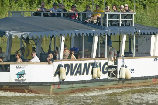 Stock Photo: 1599R-29829 Tourists on boat cruise river for hippos' at Greater St. Lucia Wetland Park World Heritage Site, St. Lucia, South Africa