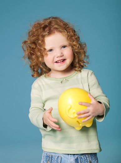 Little girl holding piggy bank : Stock Photo