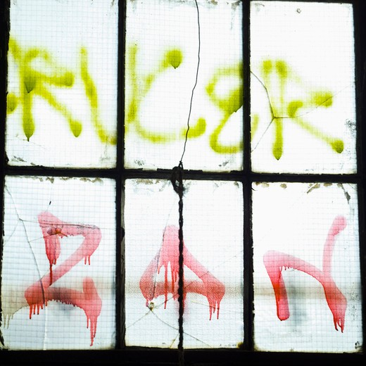 Close-up on graffitis on window pane of a disused plant : Stock Photo