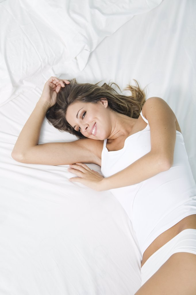 Portrait of a beautiful blonde woman waking up in bed : Stock Photo