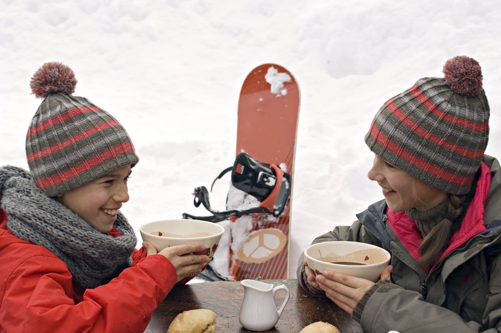 Brother and sister in ski wear eating outdoors : Stock Photo
