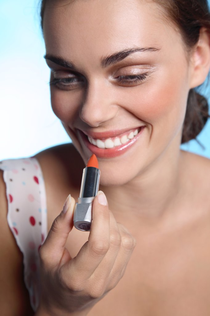 Young smiling woman applying lipstick : Stock Photo