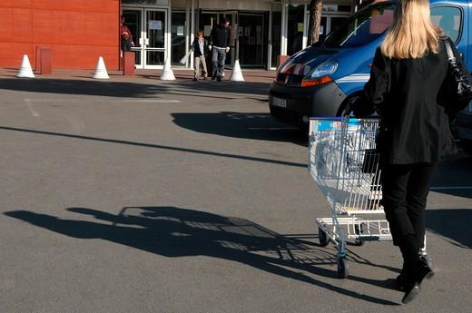 Woman pushing shopping trolley : Stock Photo