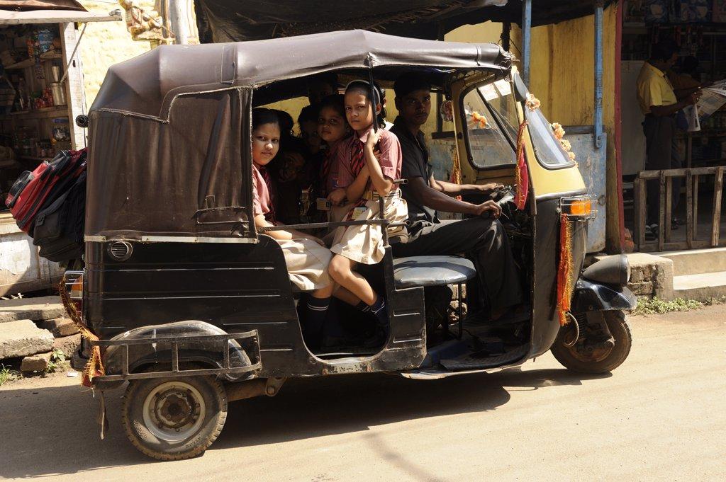 India, Orissa, Puri, children in a rick-shaw : Stock Photo