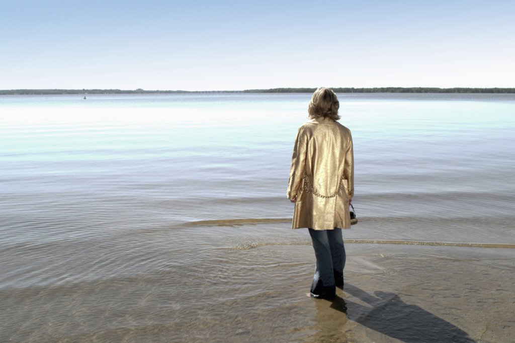Daydreaming woman by a lake : Stock Photo