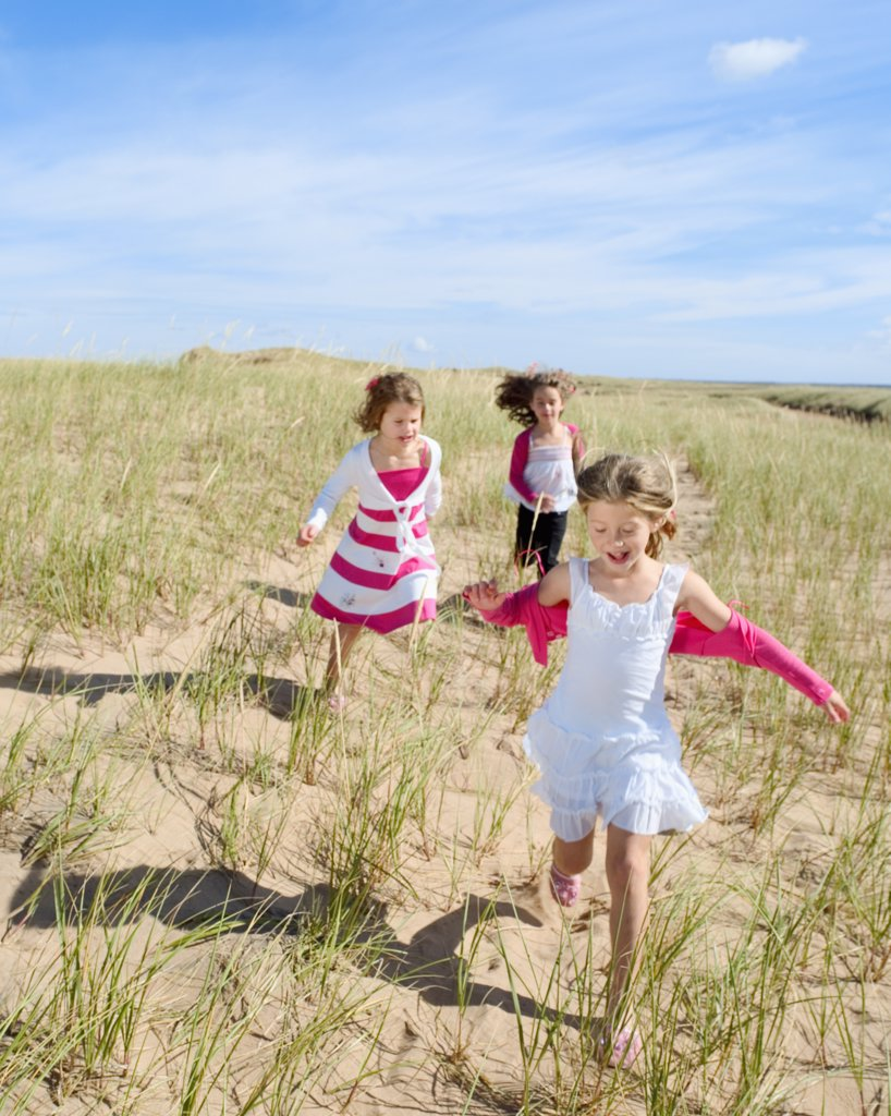 Stock Photo: 1606-109704 Three little girls running in sand dune