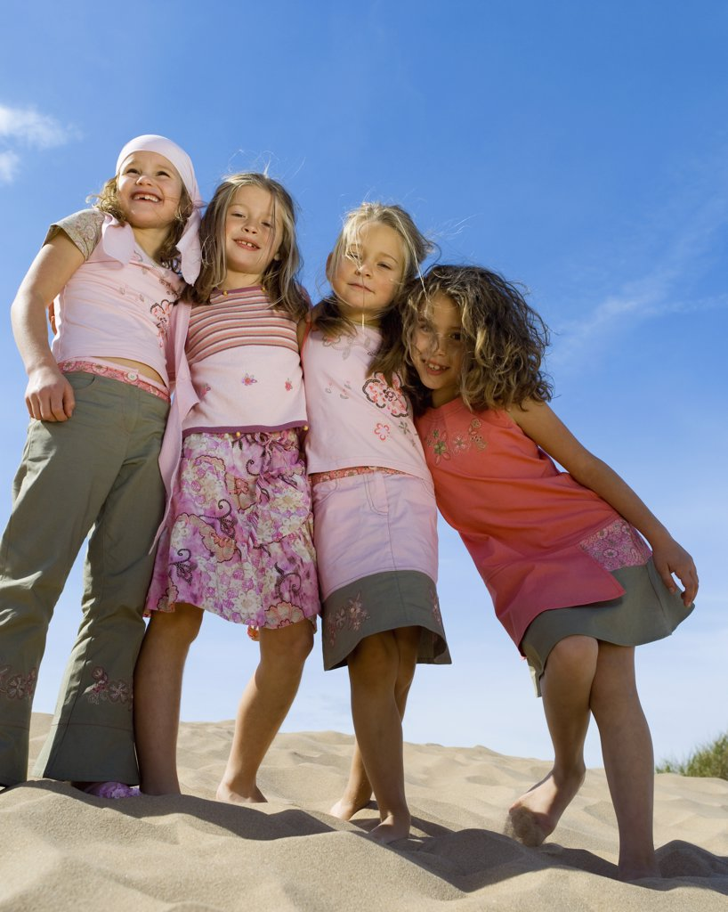 Four little girls smiling at camera on the beach : Stock Photo