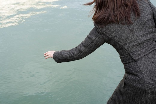 Woman wearing a coat, in front of a canal, rear view : Stock Photo
