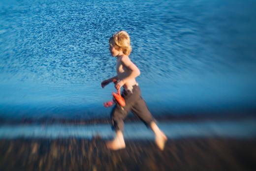 Stock Photo: 1606-112621 Boy running on seaside