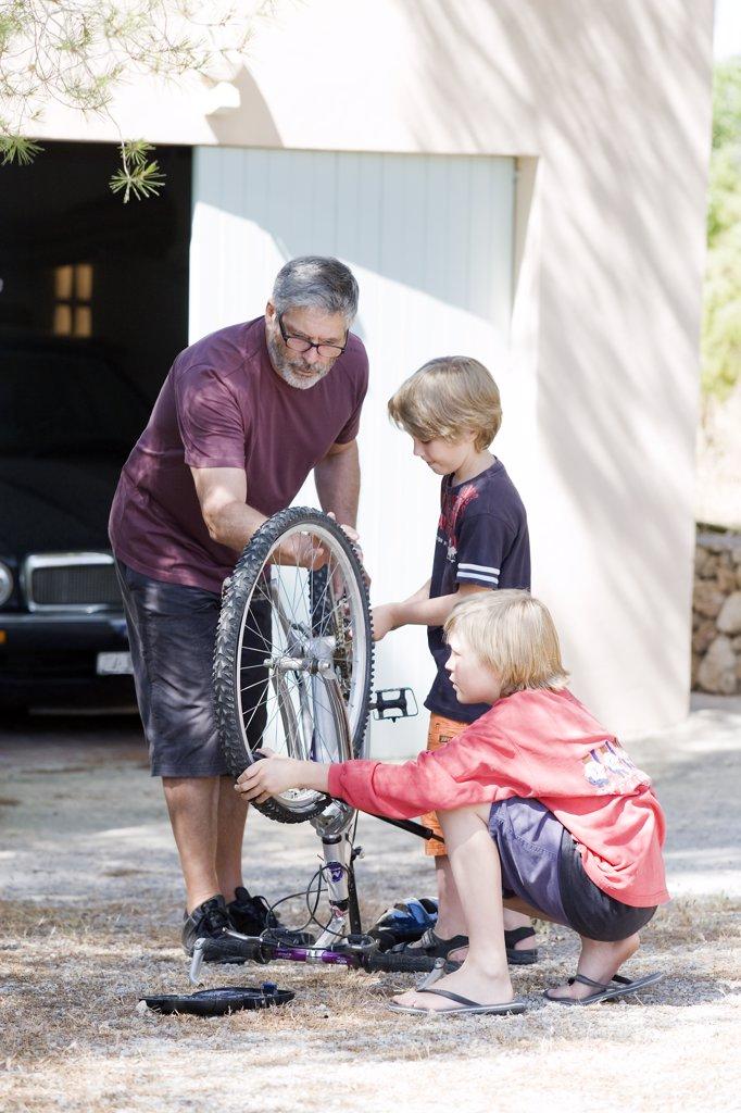 Man and children repairing bike : Stock Photo
