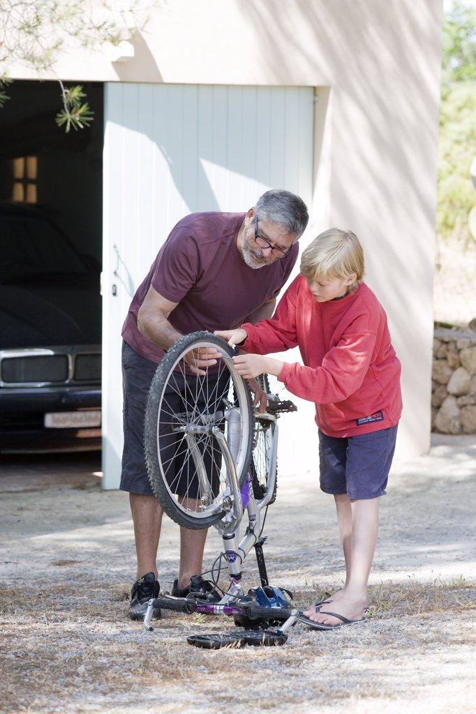 Stock Photo: 1606-113215 Man and child repairing bike