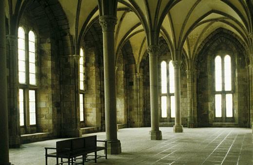 50. Mont St Michel, intérieur de la salle des hôtes (XIIIème siècle), banc en bois, arcades : Stock Photo