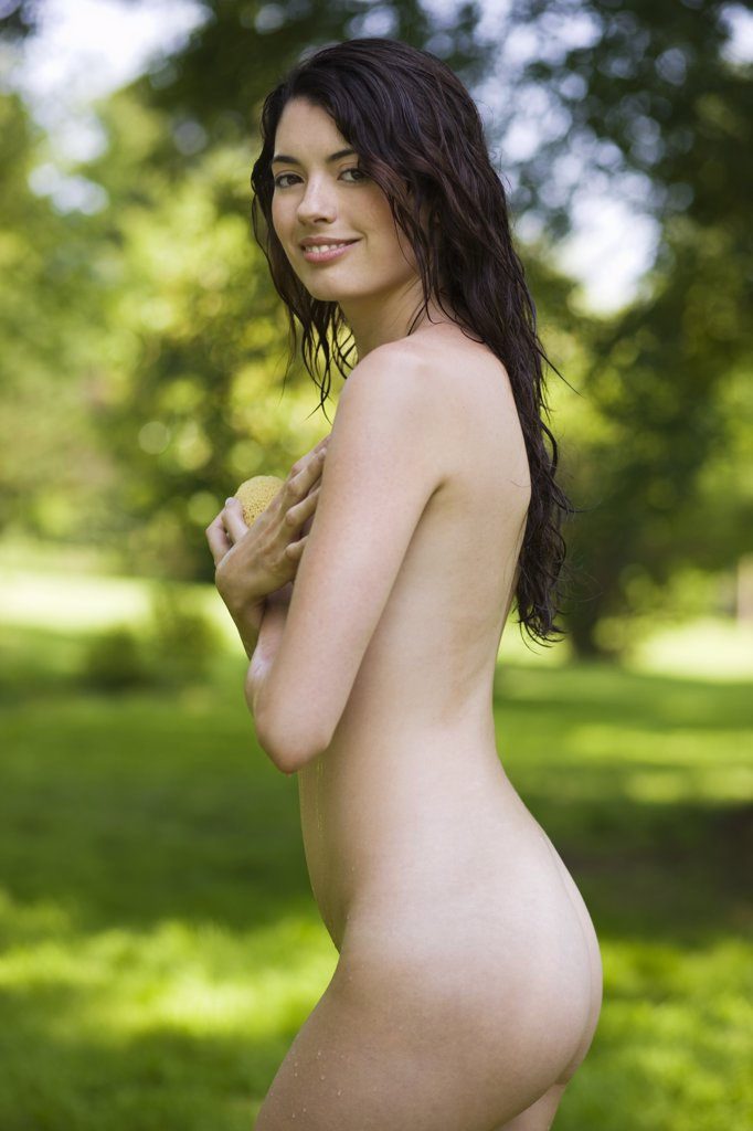 Young naked woman refreshing in green scenery : Stock Photo