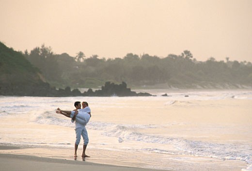 Mariane and Régis in love, in white clothes, barefoot on the shore, he is carrying her : Stock Photo