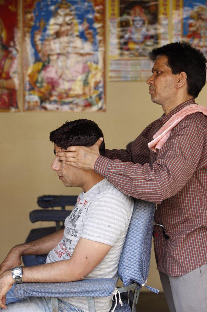 India, Uttarhakand, Rishikesh. Hairdresser giving a head massage India. : Stock Photo