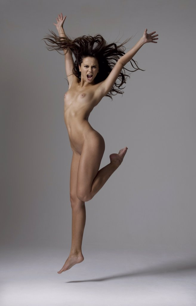 Young naked woman jumping : Stock Photo