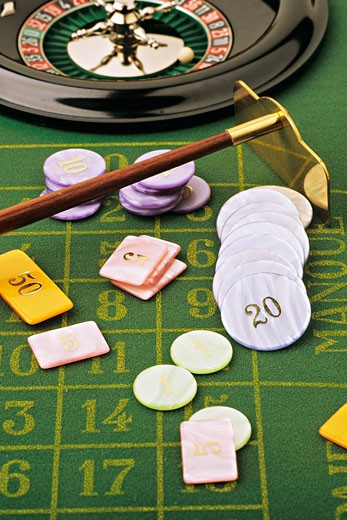 Gambling chips on a roulette table, with a roulette wheel in the background : Stock Photo