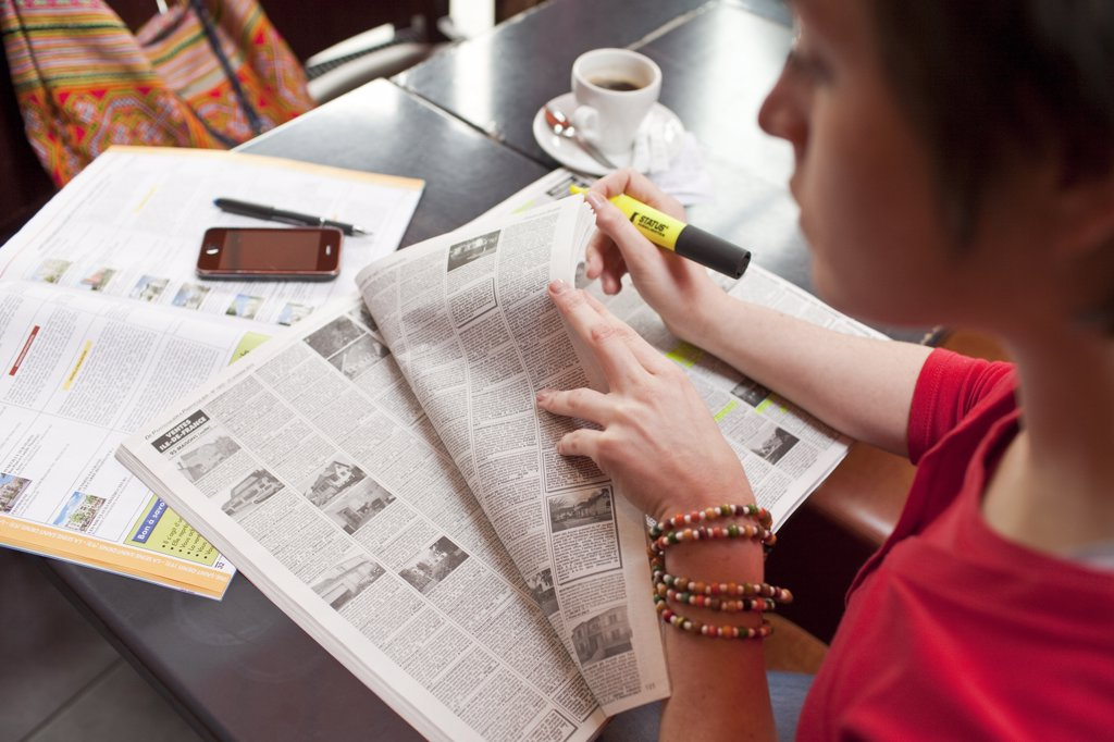 woman sitting in a restaurant and reading a classified advertisements newspaper : Stock Photo