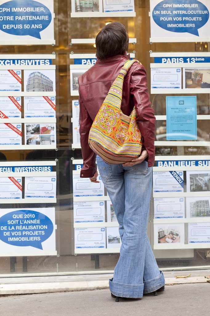 Young woman in front of an estate agent's in Paris : Stock Photo