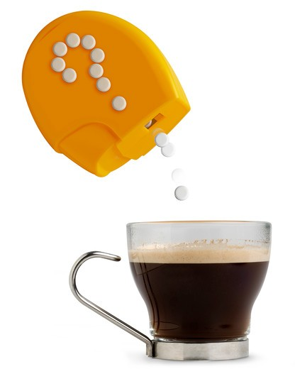 Sweeteners falling into coffee cup : Stock Photo
