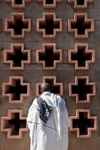 Stock Photo: 1606-136932 Ethiopia, Addis Abeba. Man praying in front of a church wall in Addis Ababa. Ethiopia.