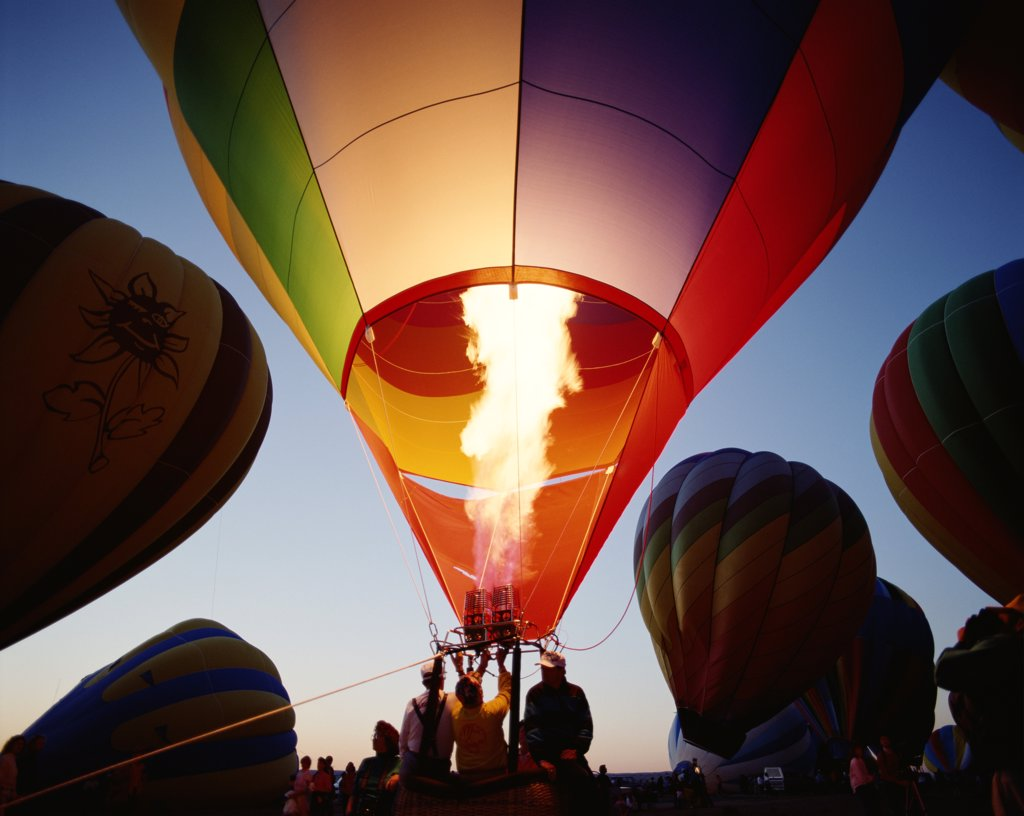 Stock Photo: 1606-145164 USA, New Mexico, Albuquerque, Colourful Hot Air Balloon being Inflated / Dusk
