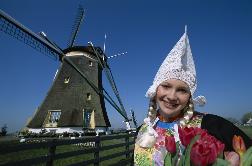 Stock Photo: 1606-149099 Holland (Netherlands), Zaanse Schans, Girl Dressed in Dutch Costume in front of Windmill