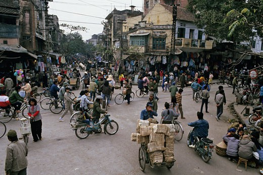 Vietnam, Hanoi, street scenery, crowd, pedestrians and motorbikes crossing the street, old traditionnal houses : Stock Photo