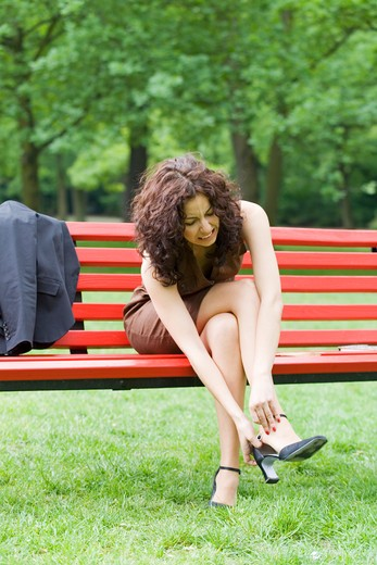 Businesswoman sitting in a bench in Park with pain in her feet because of the high heels : Stock Photo
