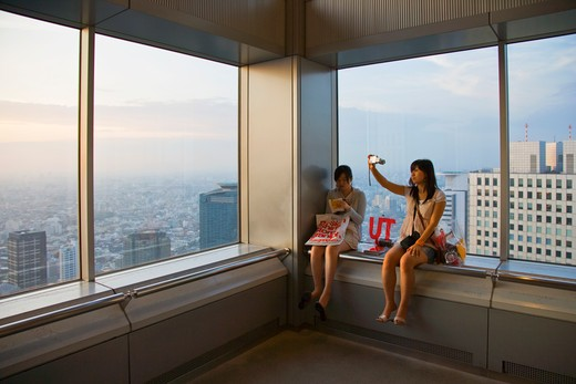Stock Photo: 1606-156167 Two young Japanese women relax at twilight in the public observatory atop the twin towers of the Tokyo Metropolitan Government Center in the Shinjuku District of Tokyo, Japan.