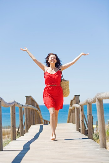 Young brunette woman arriving at the beach : Stock Photo
