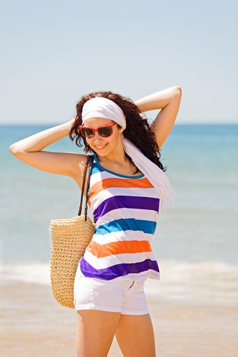 Portrait of a young brunette woman arriving at the beach : Stock Photo