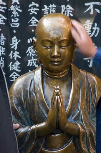 A detailed view reveals the beautiful bronze sculpturing of a Nadebotoke (Rubbing Buddha) Jizo statue, which worshippers may rub for good health, at Sensoji Temple (also known as Asakusa Kannon Temple) in Asakusa, located in the old shitamachi downt [...] : Stock Photo