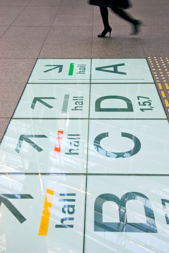 A detailed interior view reveals the laminated-glass and steel structure of the roof 60 meters above reflecting in directional signs imbedded in the floor of the Glass Building, the main entrance hall for the Tokyo International Forum (Japan's large [...] : Stock Photo