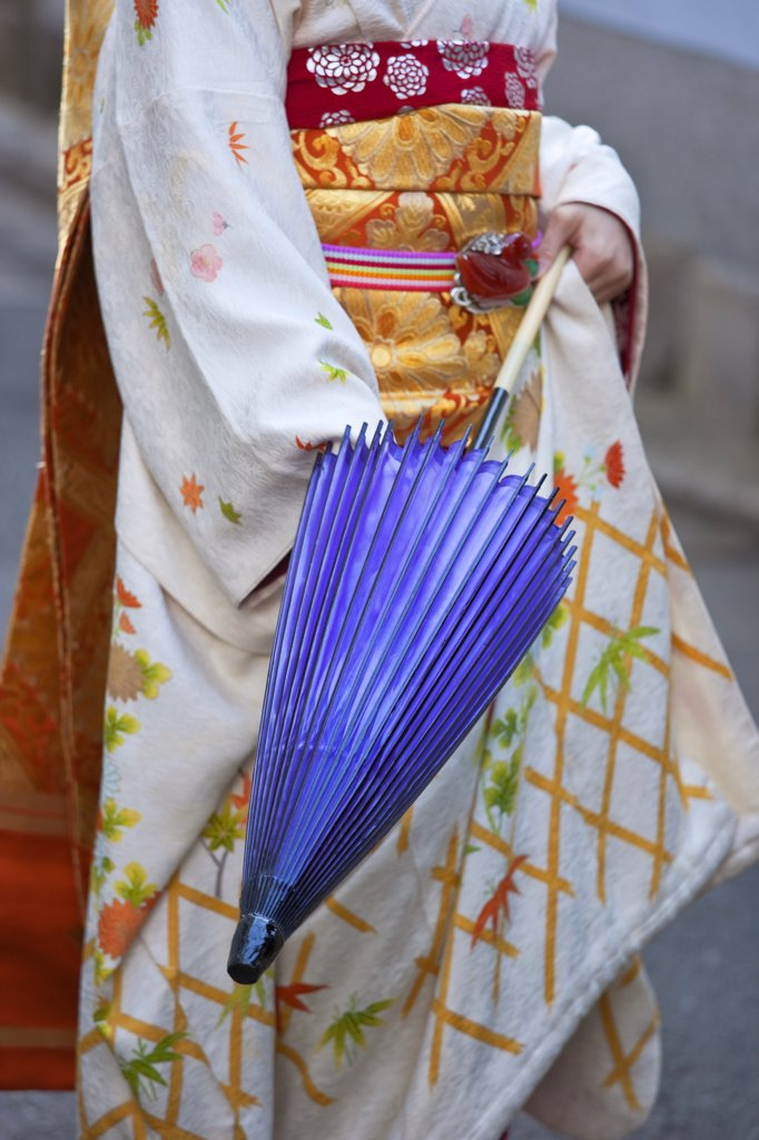 Stock Photo: 1606-157051 A maiko geisha opens a traditional paper umbrella in the Kitano district of Kyoto, Japan.