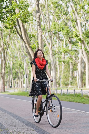 Happy woman riding with the bicycle in the city : Stock Photo