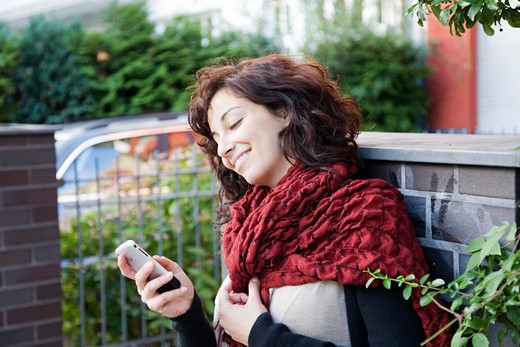 Young pretty woman texting with smartphone at the street in Berlin : Stock Photo