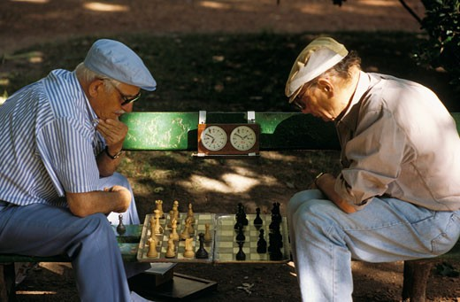Stock Photo: 1606-16346 Argentina, Buenos Aires, 2 men  sitting on a bench, facing each other, playing chess,