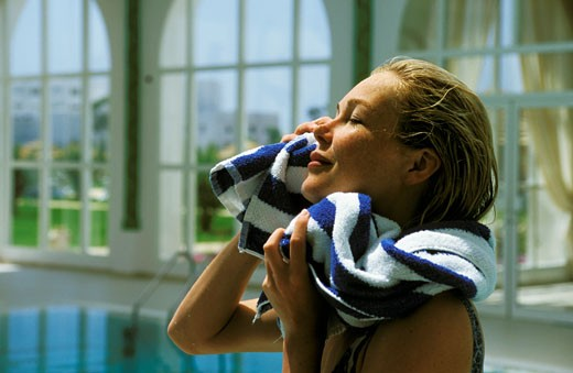Portrait of woman drying her face, indoor pool : Stock Photo