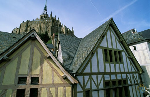 France, Normandy, Manche, Mont-Saint-Michel, timber framed houses, abbey in background : Stock Photo
