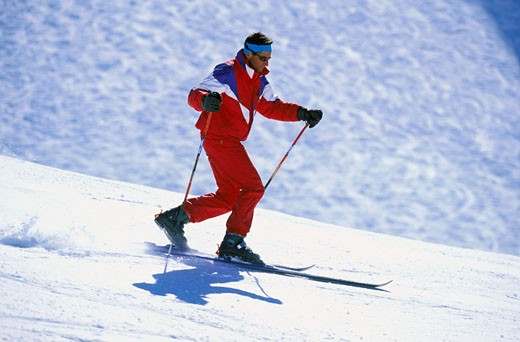 France, Alps, Haute Savoie, Grand Bornand, man in red ski jacket skiing on a piste : Stock Photo