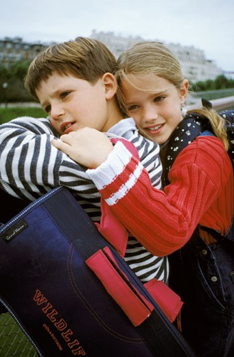 Portrait of boy and girl with school backpacks leaning against a handrail in the street, embracing : Stock Photo