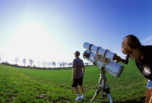 Couple observing the sun with a telescope and special glasses, greenery, fish eye effect, blue sky : Stock Photo